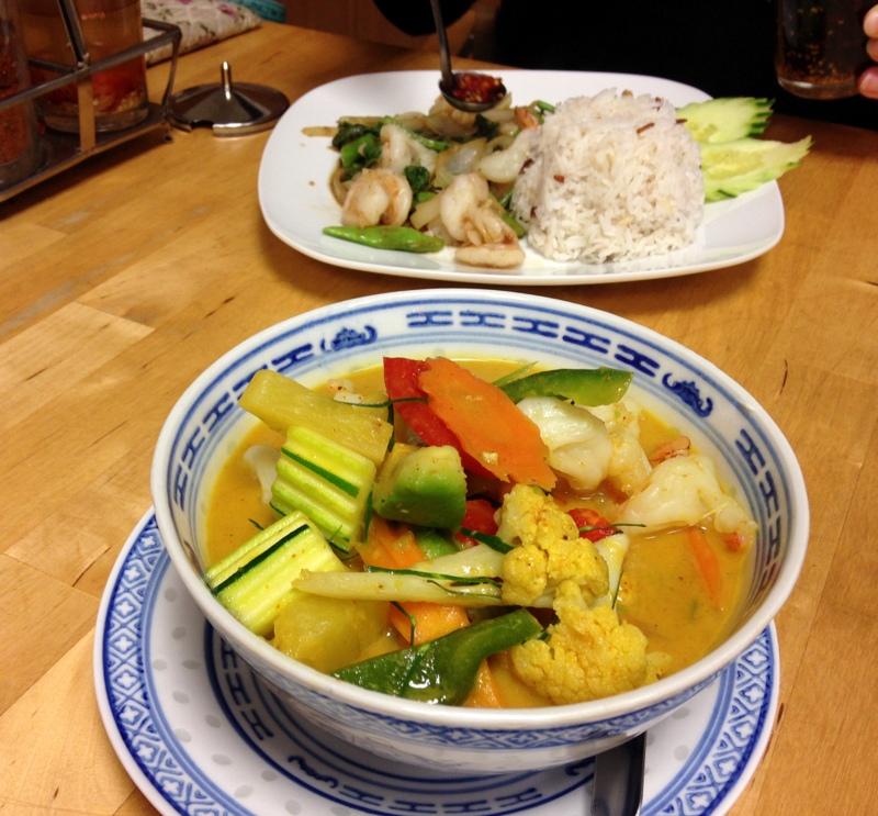 Maleewan's Thai Imbiss: Grünes Curry mit Avocado im Vordergrund, hinten Garnelen mit frischen Basilikum
