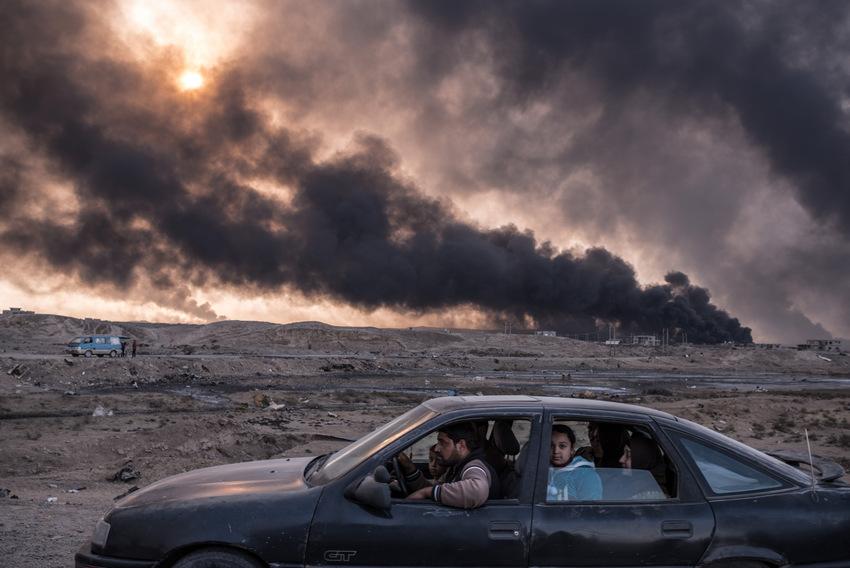 Reportagen – Zweiter Preis, Fotoserien © Sergey Ponomarev, für The New York Times Titel: Kampf um die Städte im Irak Bildunterschrift: Eine Familie auf der Flucht aus Mossul, im Hintergrund die brennenden Ölfelder von Qayyarah, 60 Kilometer südlich der Stadt, November 2016, Irak
