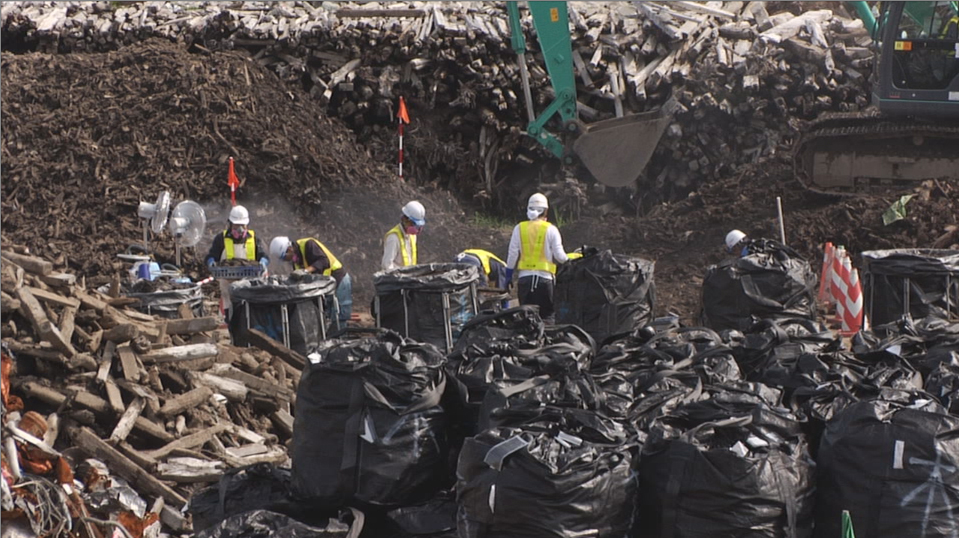 Furusato, auf der Müllhalde, schwarze Säcke mit radioaktiv verseuchter Erde und Arbeiter, Filmstill, Foto (c) imfilmagentur