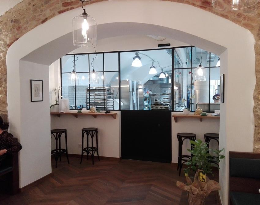 Blick vom langgestreckten Gastraum auf die Schiebetür ins Allerheiligste, die Backstube des Parémi, Bild (c) Claudia Busser - kekinwien.at