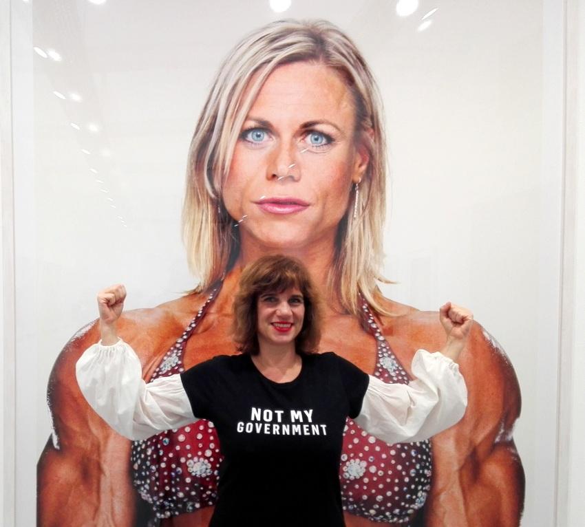 Beatrix Roidinger von E.R.O.S. & du in einem Shirt von Modus Vivendi vor einem Foto aus der Serie 'Female Bodybuilder', Bild (c) Claudia Busser - kekinwien.at